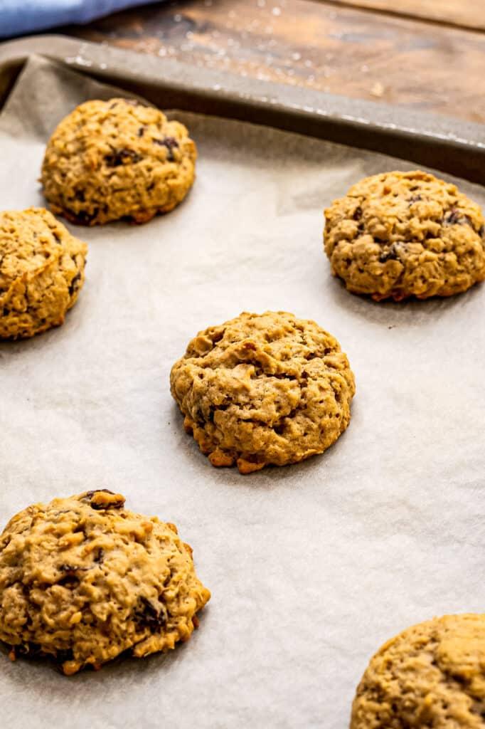 Baking sheet with baked oatmeal raisin cookies on it