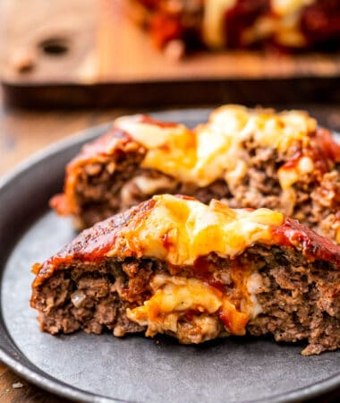 A plate with cheese stuffed Italian meatloaf on it.