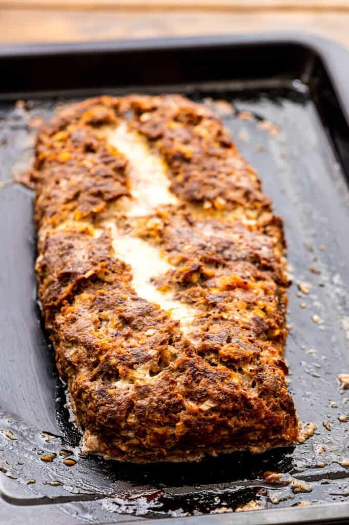 Baked cheese stuffed Italian meatloaf on pan.