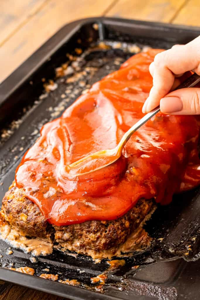 Spoon spreading tomato sauce on top of Italian meatloaf
