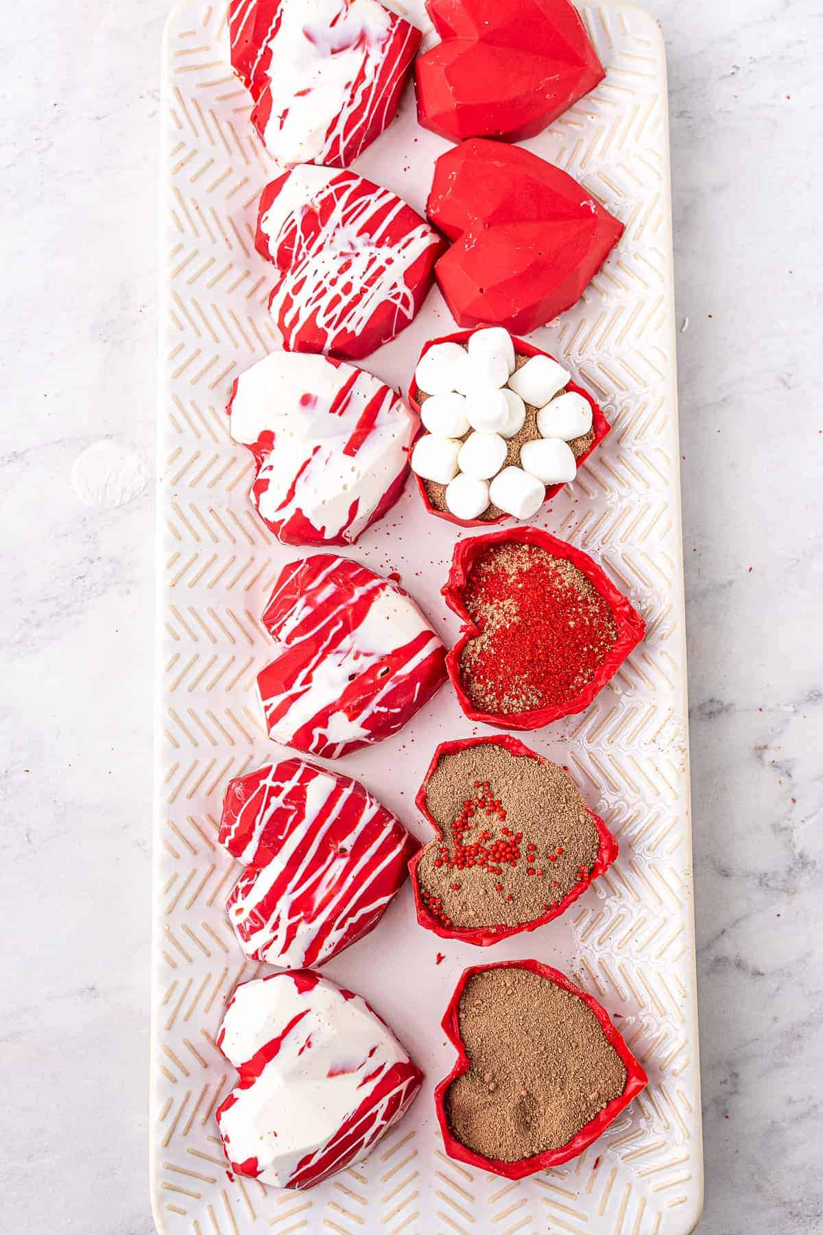 Heart Hot Chocolate Bombs halves with hot cocoa mix and mini marshmallows in them