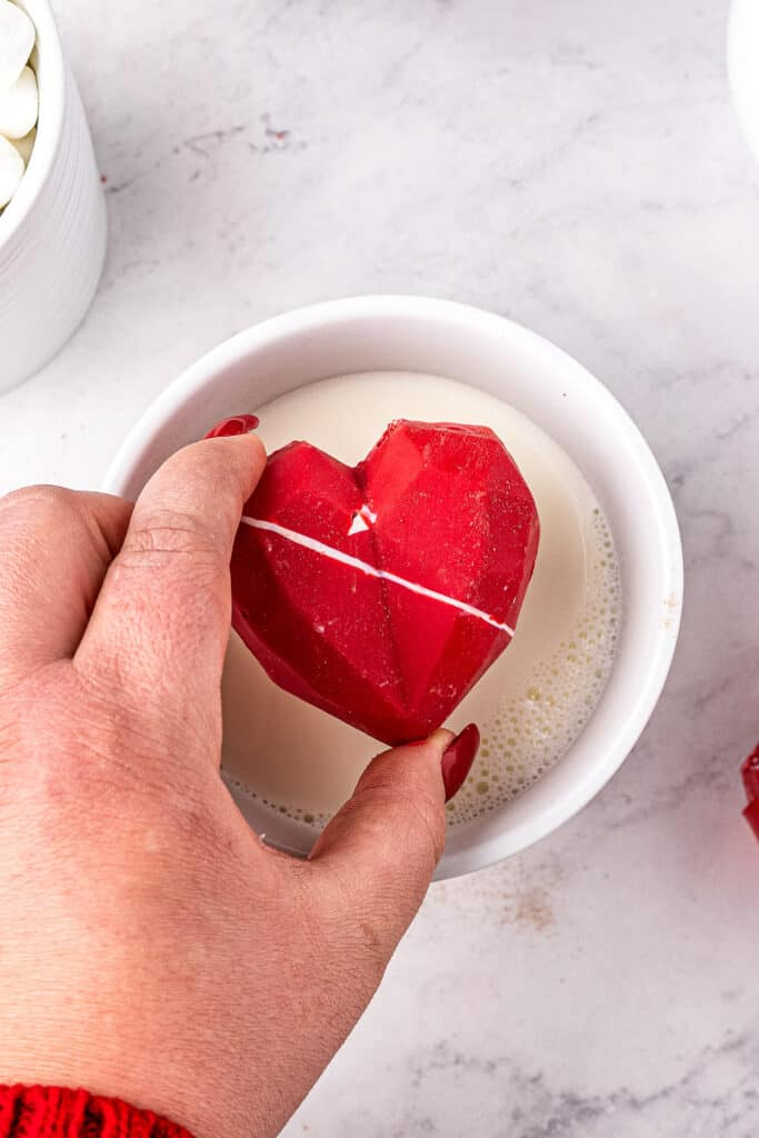 Hand dropping Valentine's Day Hot Chocolate Bomb into mug of milk