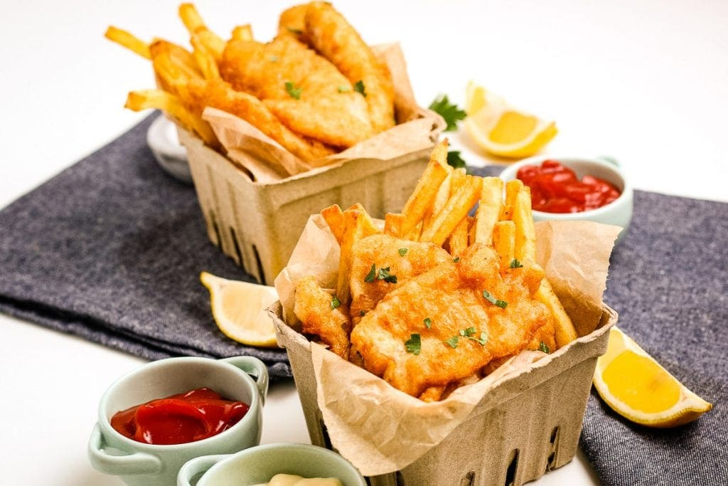 Beer Battered Fish and Chips  in cardboard containers with containers of ketchup and lemon slices beside them.