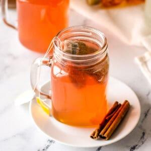 Starbucks Medicine Ball Tea in a mason jar on a white plate with cinnamon sticks
