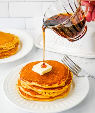 Small pitcher pouring syrup over the top of cornmeal pancakes