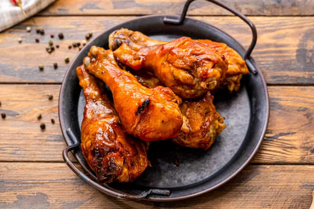 BBQ Chicken legs on black serving dish with handles