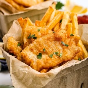 Beer Battered Fish and Chips in cardboard containers and garnished with parsley.