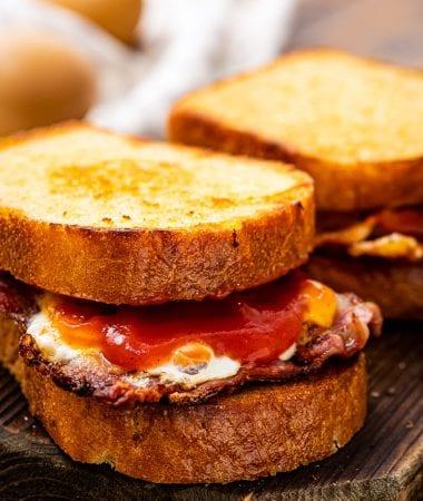 Fried Egg Sandwich sitting on a piece of wood cutting board.