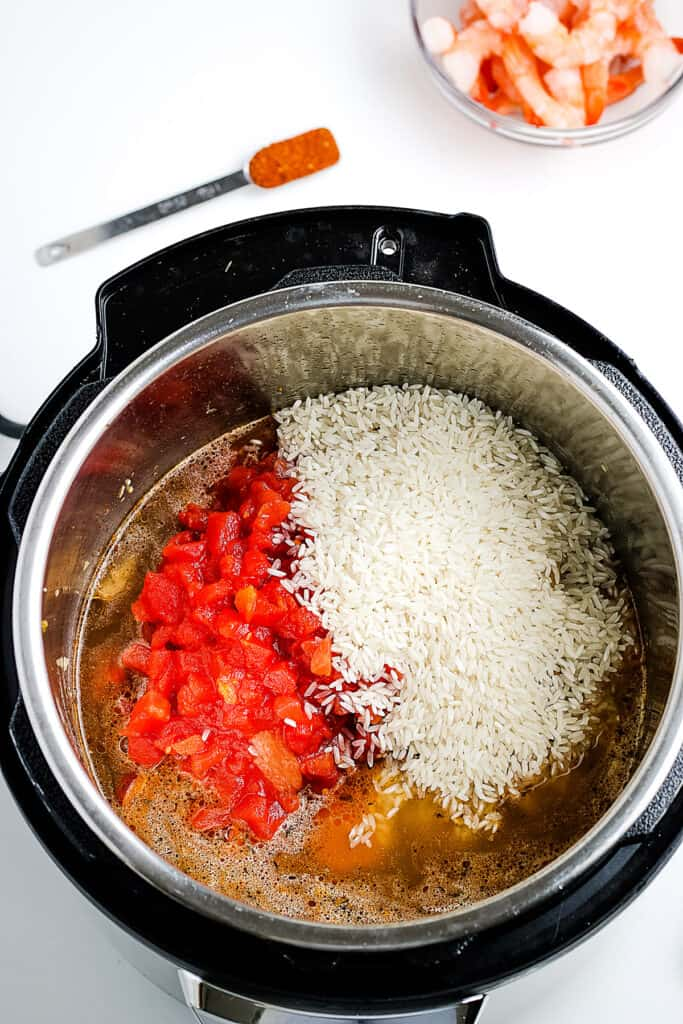 Diced tomatoes and rice added to pressure cooker