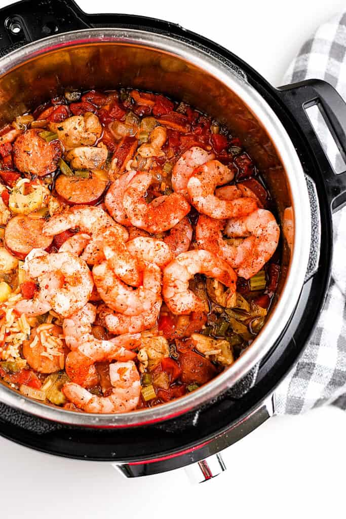 Add shrimp and seasonings to jambalaya in pressure cooker