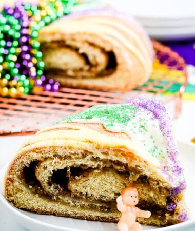 Slice of King Cake on a white plate with plastic baby