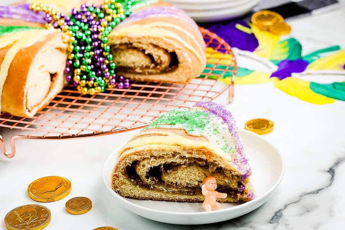 King Cake slice on white plate with full cake behind it