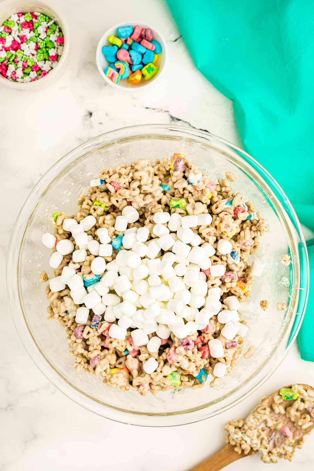 Overhead image of marshmallow and lucky charms mixture with extra mini marshmallows on top