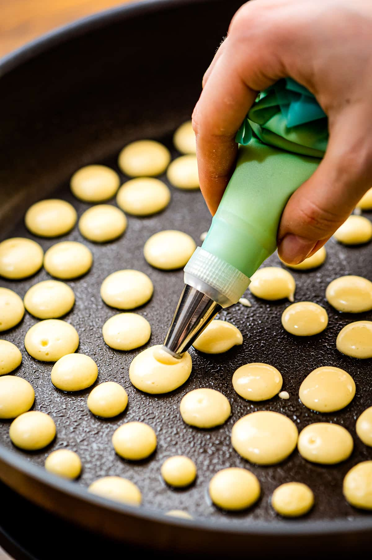 Squeeze mini pancakes into a skillet with piping bag