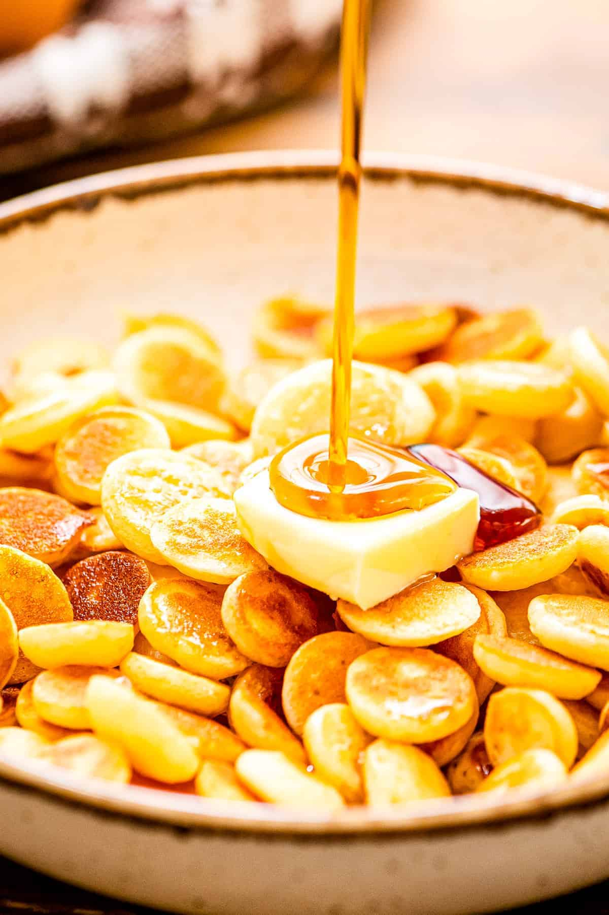 A bowl of mini pancake cereal with a slab of butter and syrup being poured on