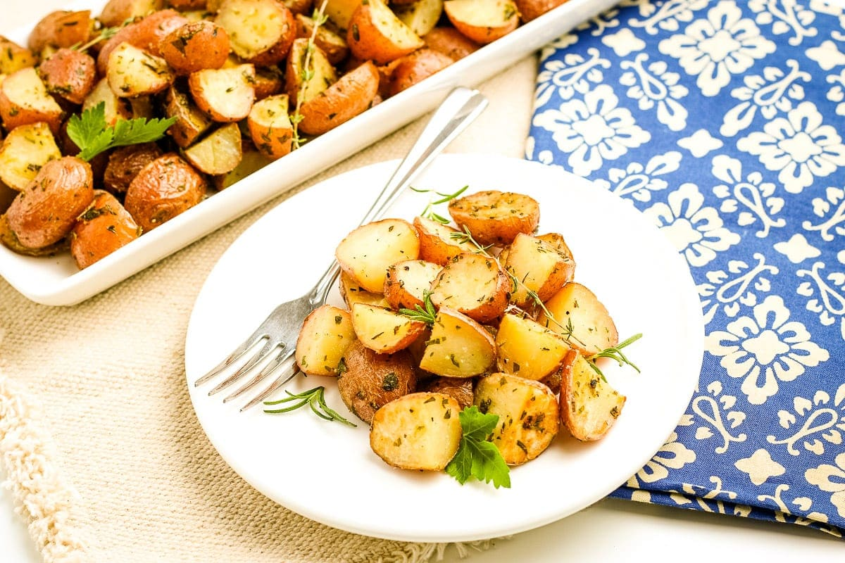 Oven Roasted Potatoes on white plate with fork on it. A serving platter of more potatoes in background and blue napkin.