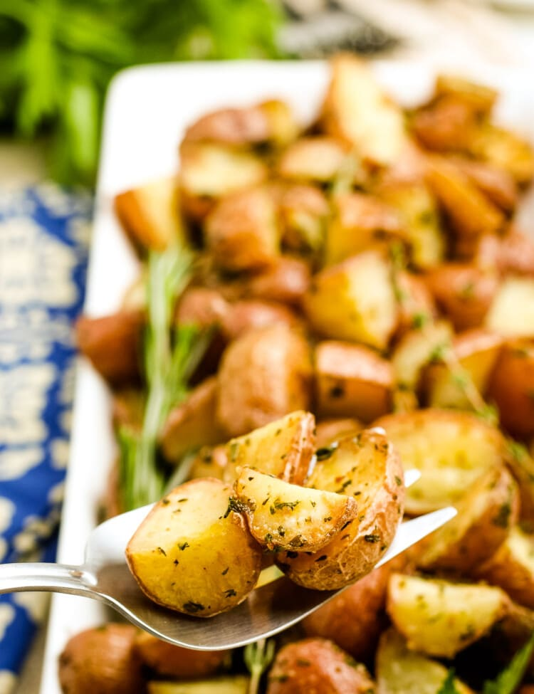 Oven Roasted Potatoes on a serving spoon with a platter of more potatoes in background