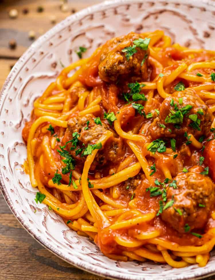 Bowl of spaghetti and meatballs topped with parsely