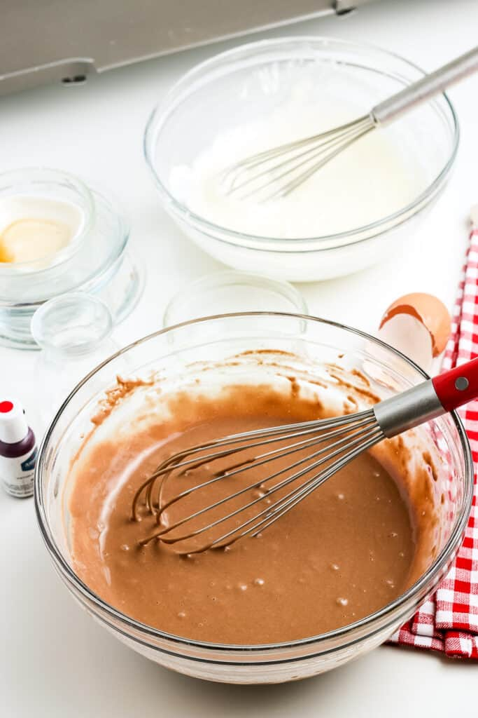 Glass bowl with batter for red velvet pancakes with whisk in it