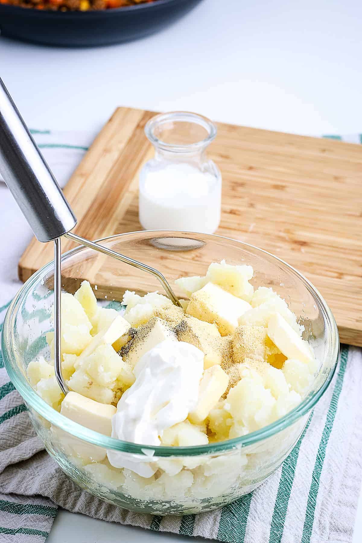 A glass bowl with ingredients to make mashed potatoes