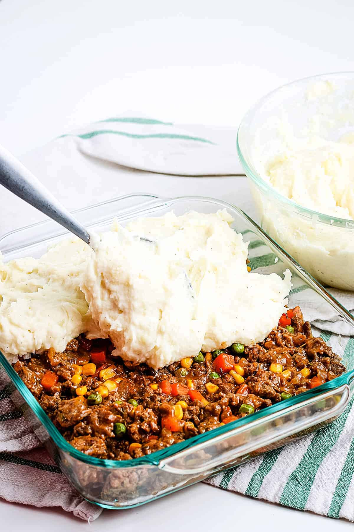 Spreading mashed potatoes on ground beef mixture in glass baking dish