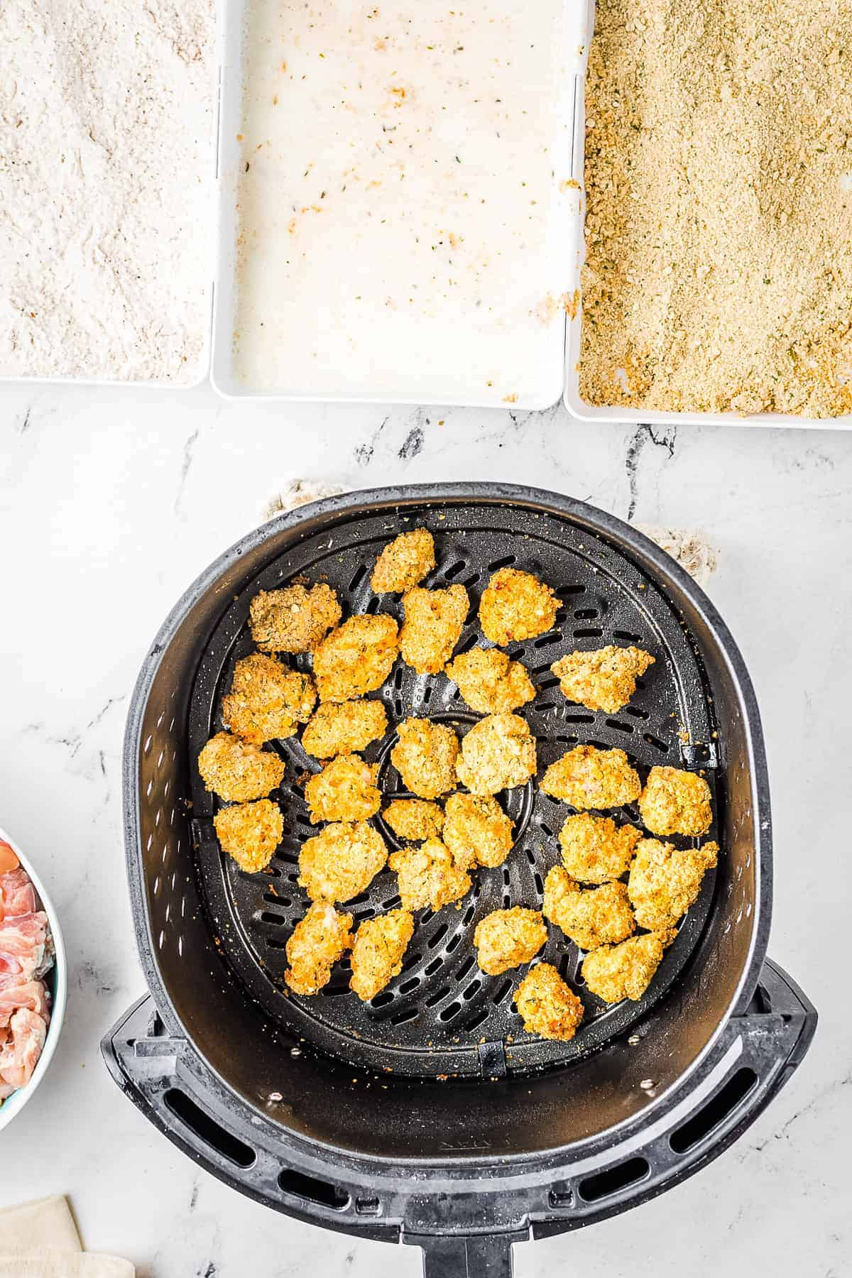 Cooked chicken nuggets in air fryer basket