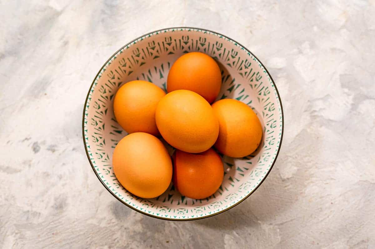 An overhead image of brown eggs in a bowl