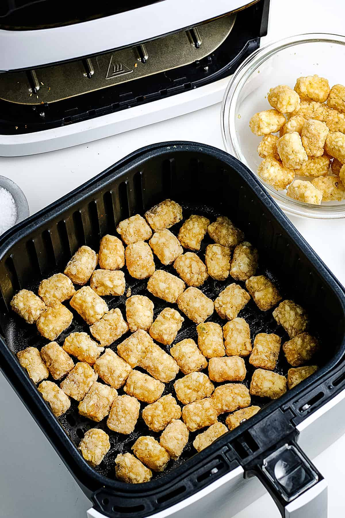 Raw Tater Tots in air fryer basket