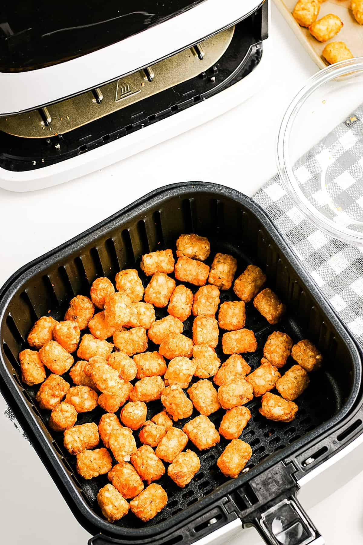 Cooked Tater Tots in air fryer basket