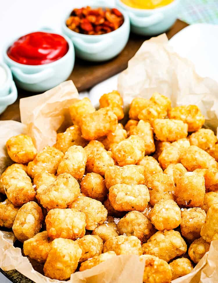 Air Fryer Tater Tots in a basket lined with brown paper and condiments behind