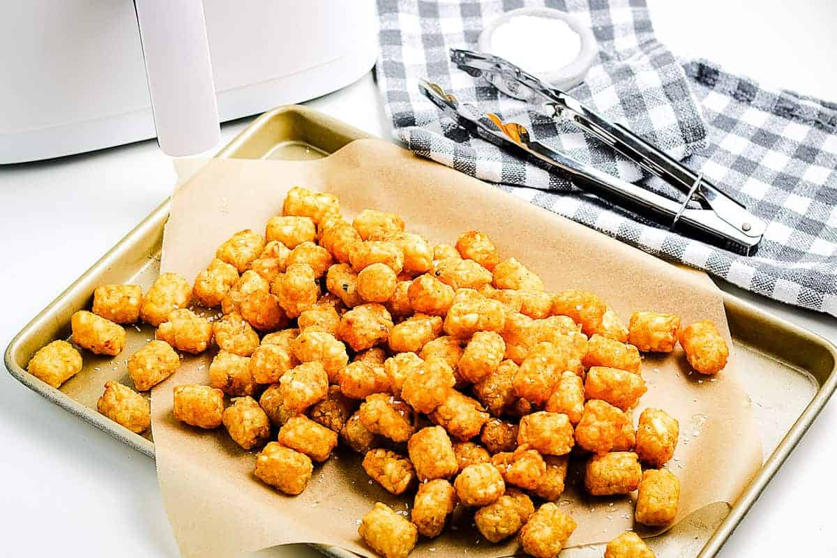 A sheet pan lined with brown paper with crispy tater tots on top