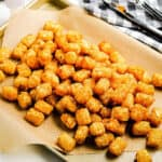Square cropped image of Air Fryer Tater Tots on a brown piece of paper on sheet pan