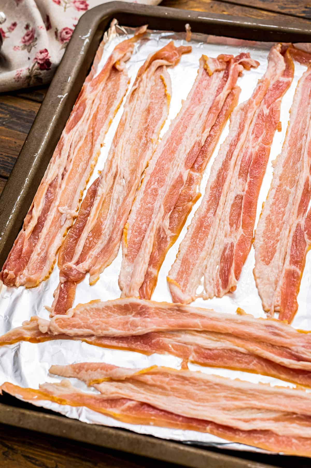 Raw Bacon Strips on a sheet pan lined with foil