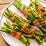 Square cropped image of bacon wrapped green beans on white plate