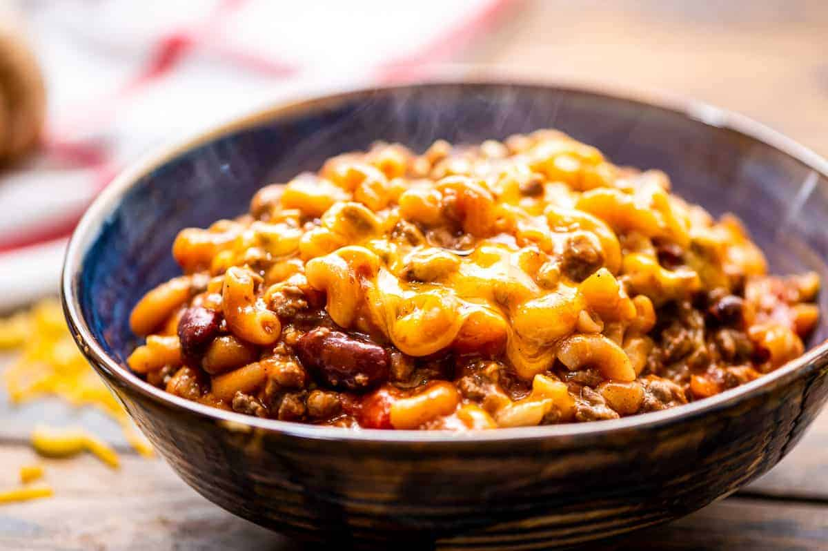 A bowl with steaming chili mac topped with cheese