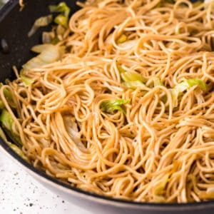 Close up image of chow mein noodles in black skillet