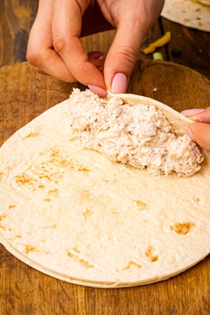 Pair of hands rolling up chicken enchilada