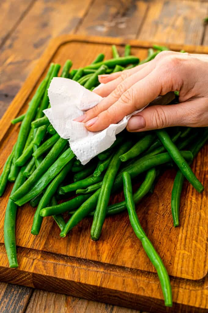 Drying off green beans with paper towel