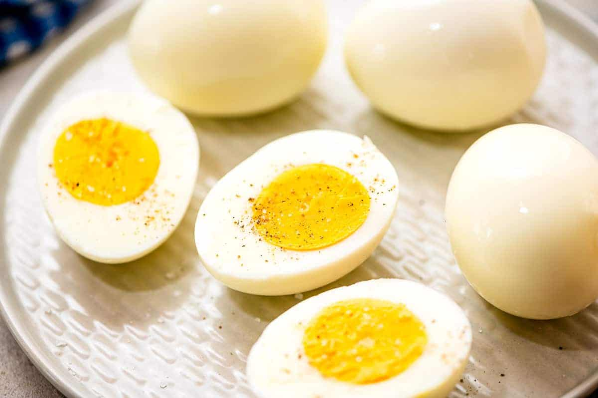 A white plate with three Hard Boiled Eggs cut in half