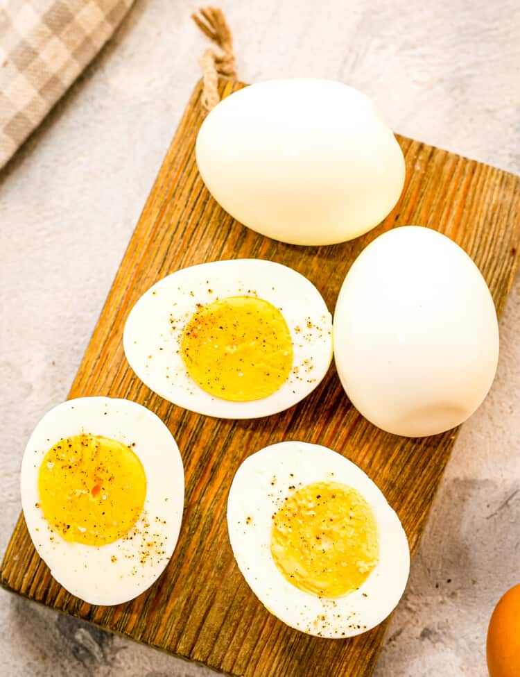 A brown wood cutting board with hard boiled eggs cut open with salt and pepper