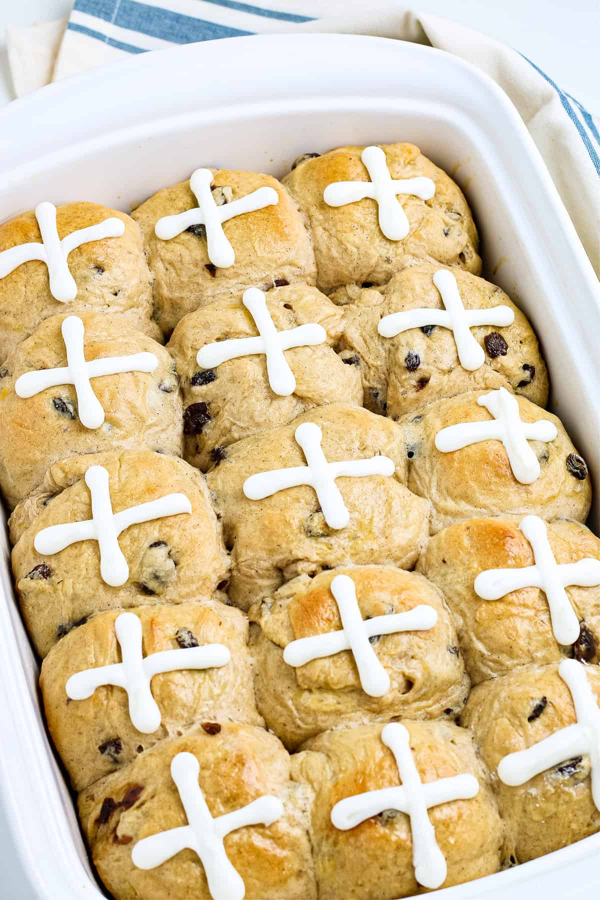 Pan of hot cross buns topped with an icing of a cross