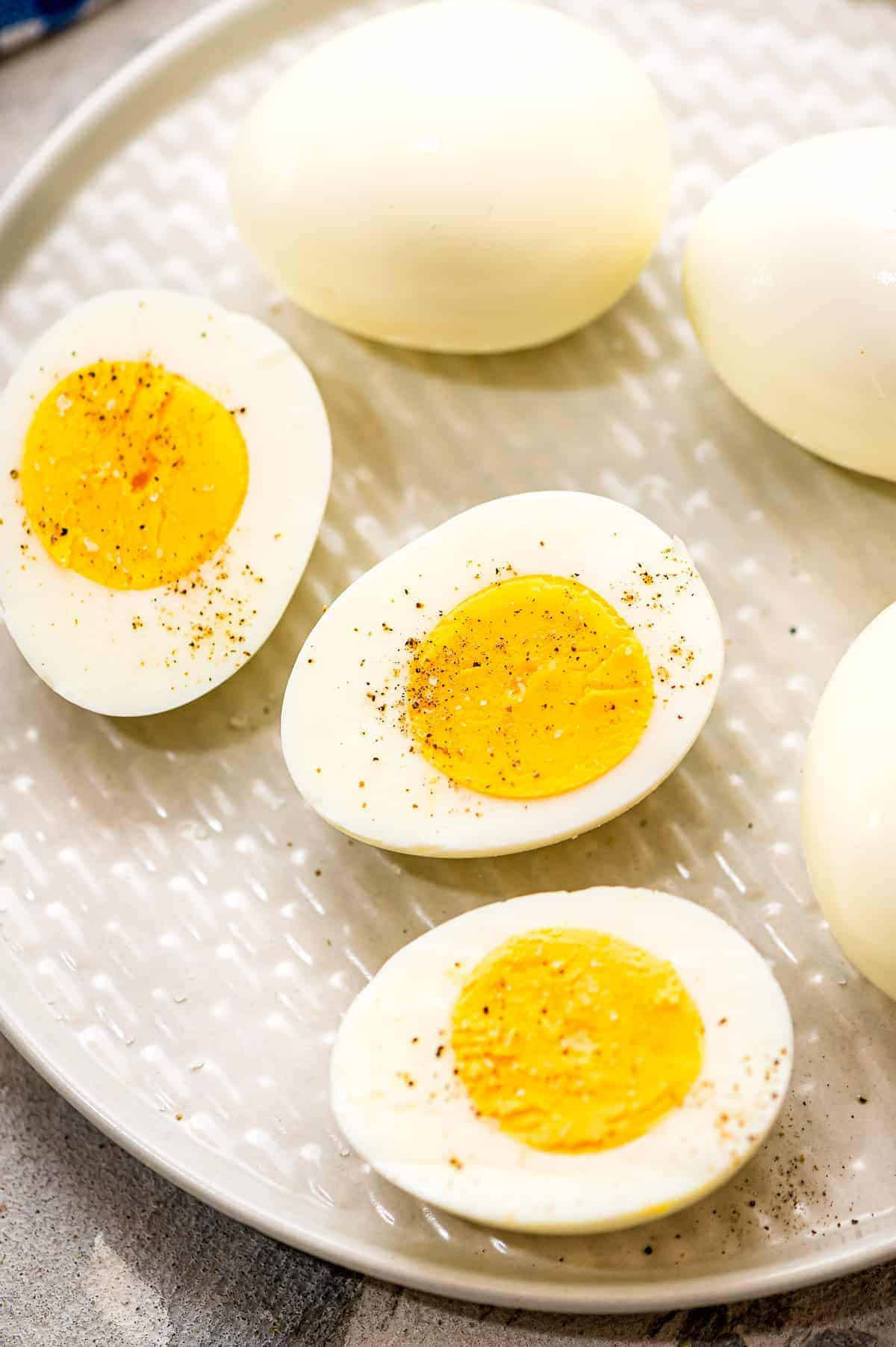 Hard Boiled Eggs cut in half sprinkled with salt and pepper on plate