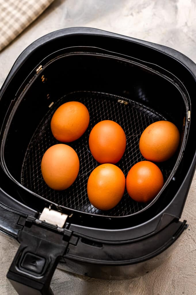 Air fryer basket with brown eggs in it