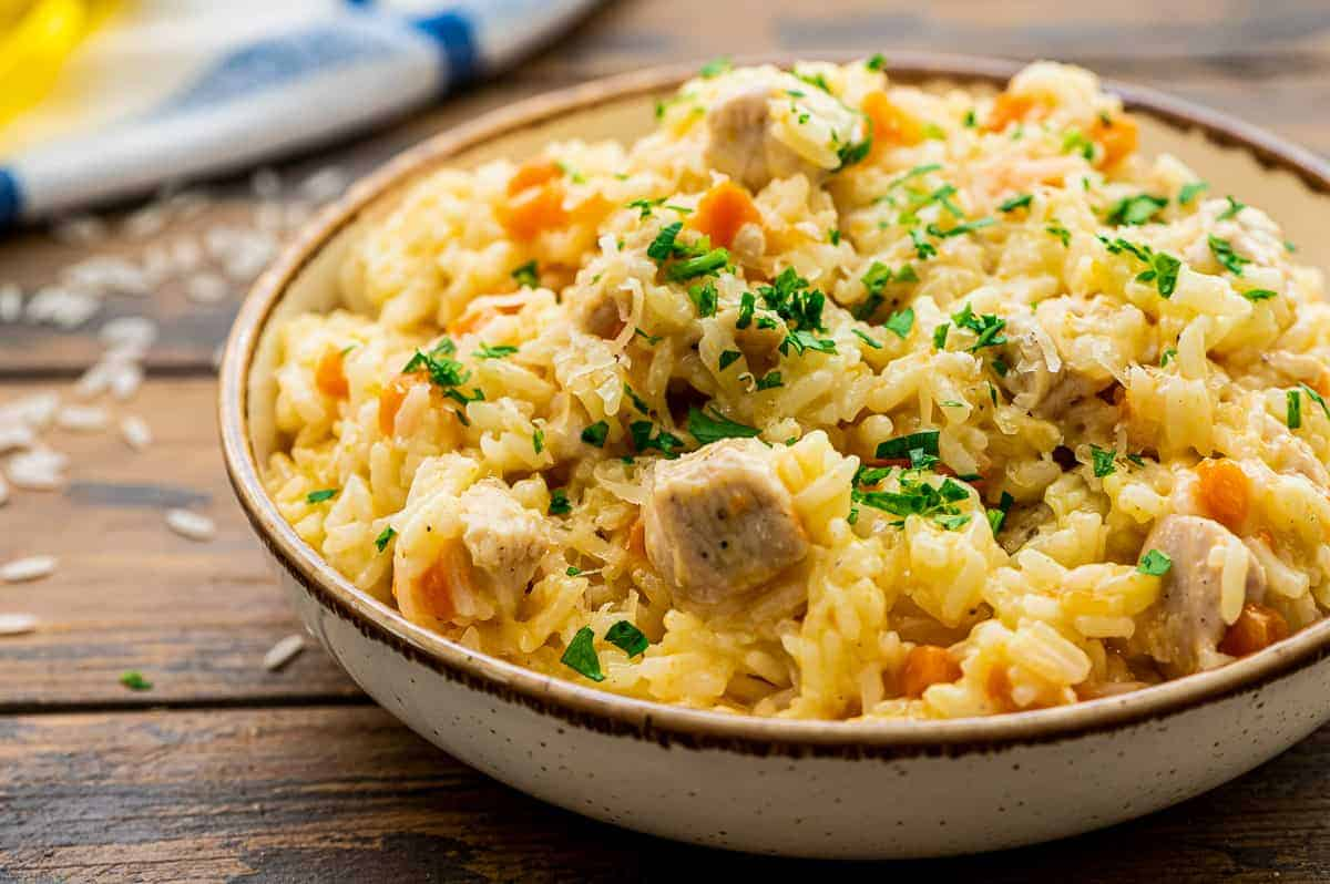 Bowl of chicken and rice topped with chopped parsley