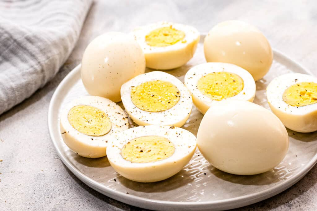 Plate with hard boiled eggs that are cut open and seasoned with pepper