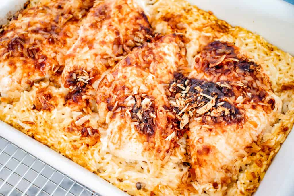White casserole dish with no peek chicken and rice in it
