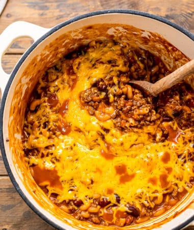 Overhead image of chili mac in dutch oven with wooden spoon