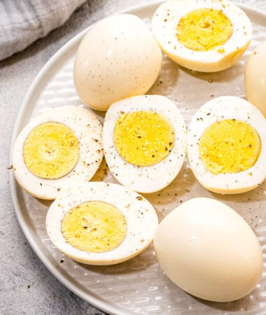 Hard Boiled Eggs with some cut in half on a plate and seasoned with pepper