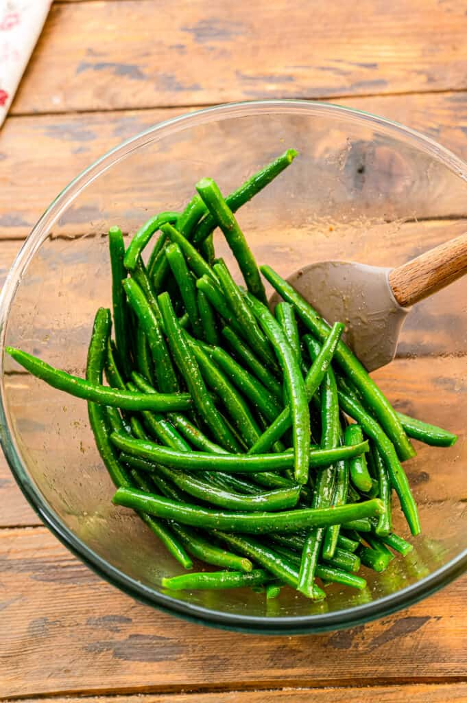 Mixing green beans in glass bowl with seasonings