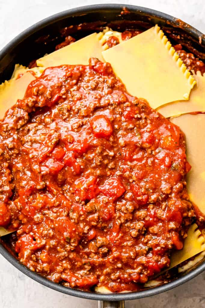 Topping lasagna noodles with meat sauce in skillet